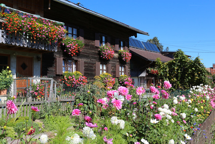 Perennial Garden With Hanging Baskets Of Annuals.